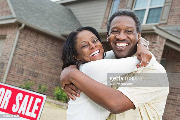 Happy senior African American couple outside recently purchased home