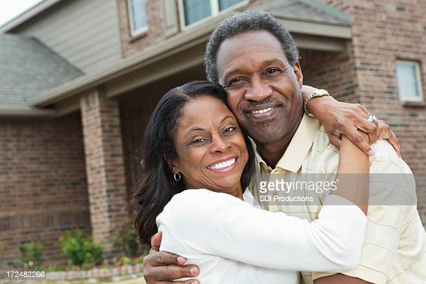 Happy senior African American couple standing outside home