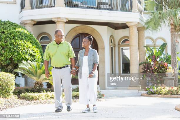 Happy senior African-American couple in front of home