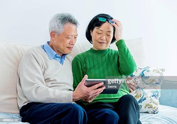 Happy senior asian couple reading on a digital tablet