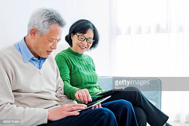 Happy senior asian couple reading on a digital tablet
