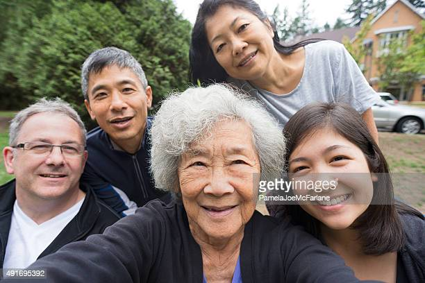 Happy Senior Asian Woman Taking Selfie with Family in Park