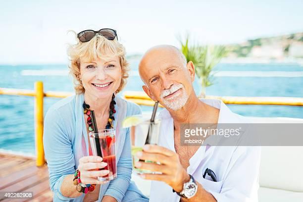 Happy senior couple at beach cocktail bar