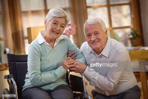 Happy senior couple at home looking at camera