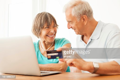 Happy senior couple buying on the internet : Stock Photo