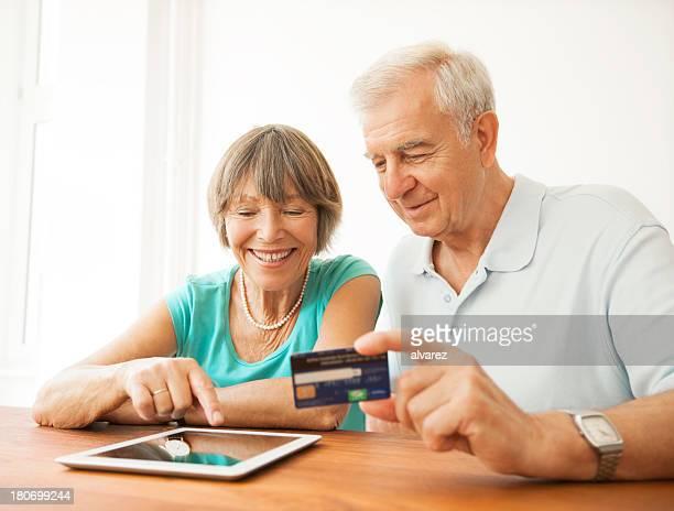 Happy senior couple buying on the internet