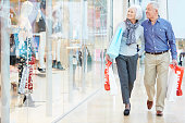 Happy Senior Couple Carrying Bags In Shopping Mall Relaxing