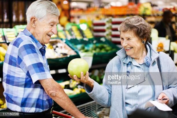 Felice coppia senior scegliere pompelmo sezione di frutta in Supermercato