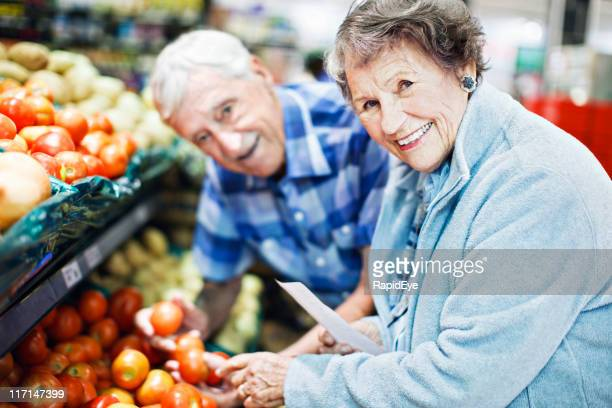 Happy senior couple choosing tomatoes in supermarket look up, smiling