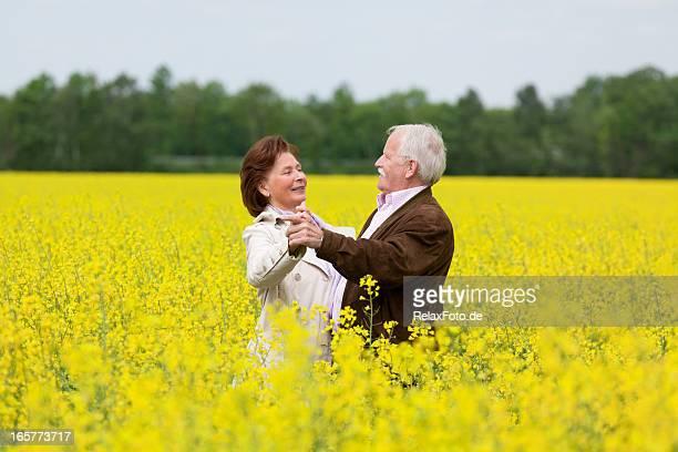 Happy Senior couple dancing in blooming canola field (XXXL)