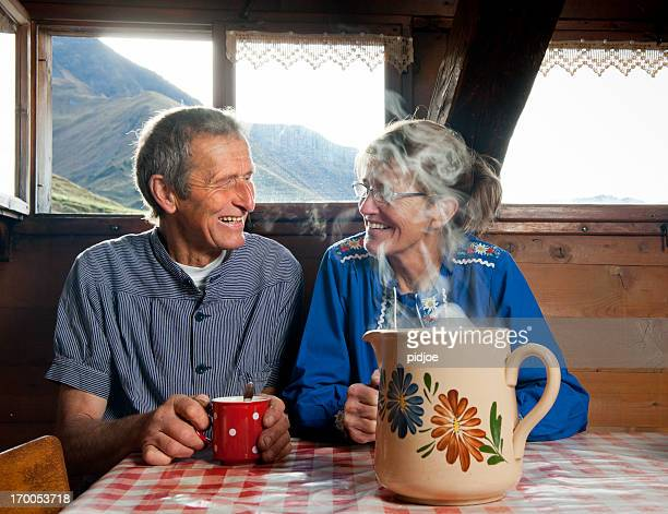 happy senior couple drinking coffee in farmhouse