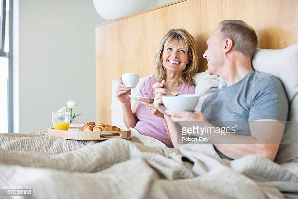 Happy senior couple enjoying breakfast in bed
