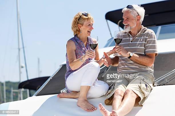 Feliz pareja senior disfrutando de vino en yate