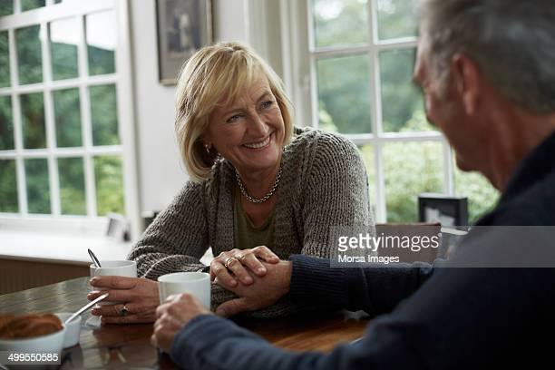 Happy senior couple having coffee in cottage
