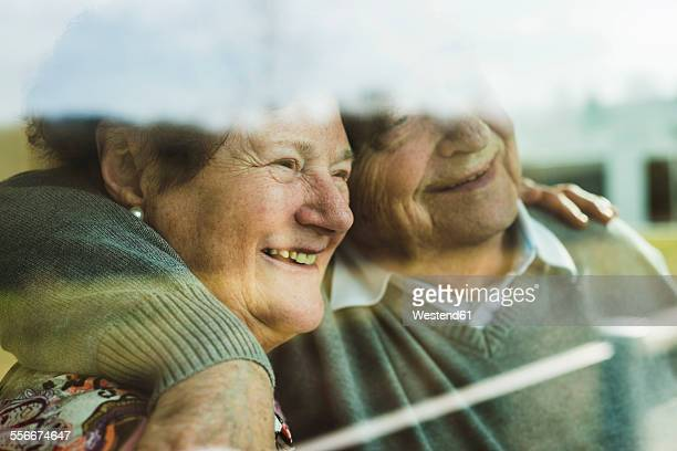 Happy senior couple head to head looking through window