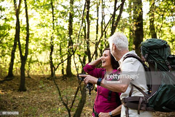 Happy senior couple hiking in a forest