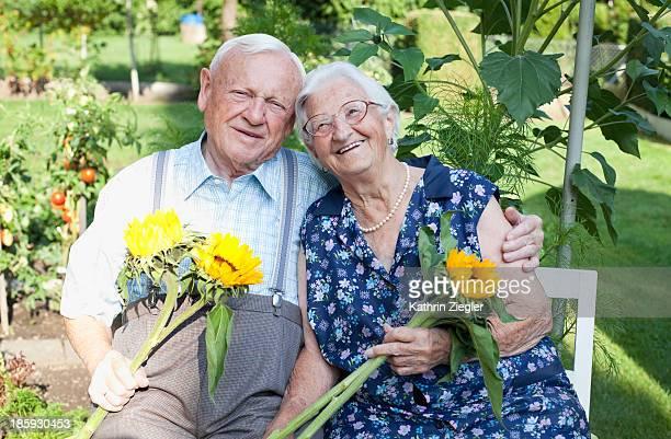 happy senior couple holding freshly cut sunflowers