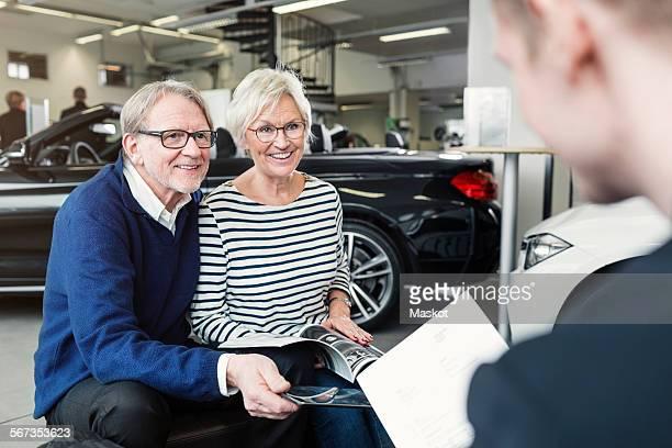 Happy senior couple looking at salesman in car showroom