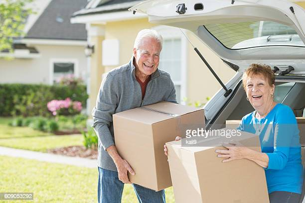 Happy senior couple moving boxes in car