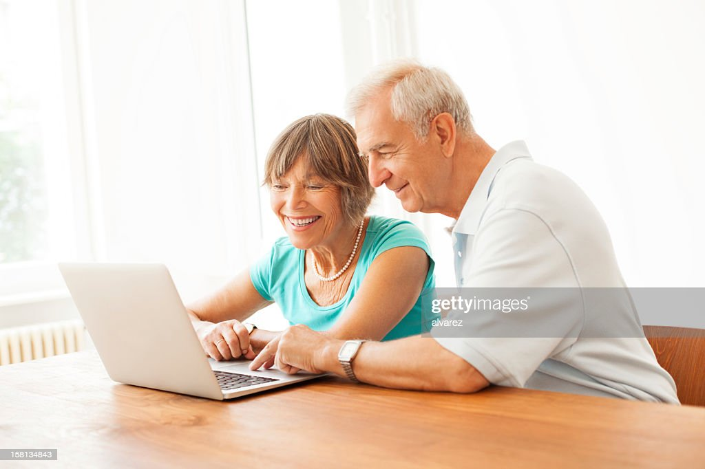 Happy senior couple navigating the internet : Stock Photo