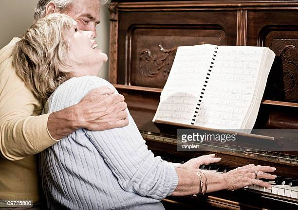 ハッピーな年配のカップルのピアノ演奏