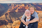 Happy, Hugging Senior Couple Posing on the Edge of The Grand Canyon.