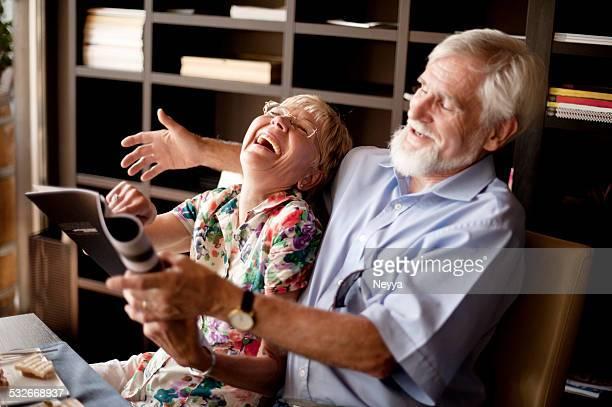 Heureux Couple âgé lisant un Magazine dans le Bar