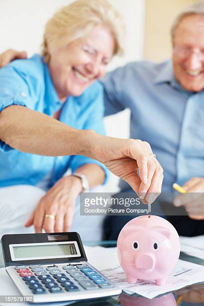 Happy senior couple saving money at home