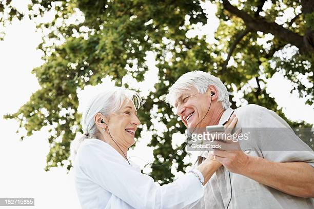 Happy Senior Couple Sharing einen Audio-Player im Freien