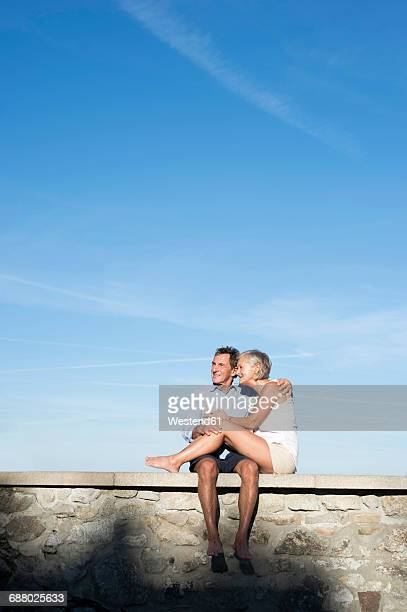 Happy senior couple sitting barefoot on a wall in front of sky