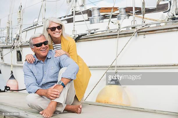 Happy senior couple sitting on boat dock