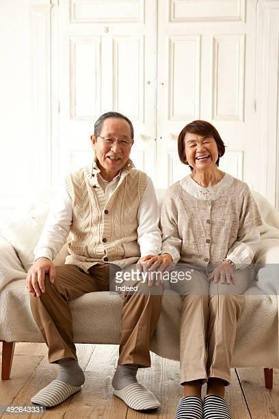 Happy senior couple sitting on sofa