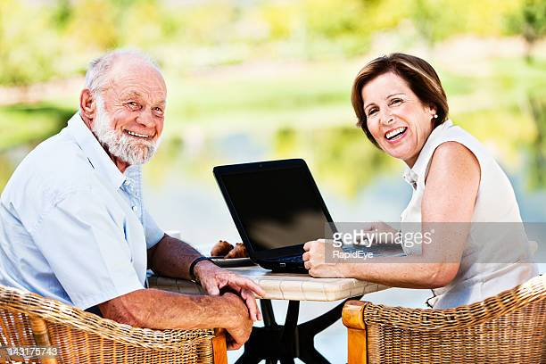 Happy senior couple sitting outdoors sharing laptop computer look round