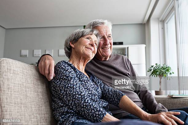 Happy senior couple sitting together on the couch at living room