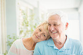 Happy romantic senior couple smiling at home