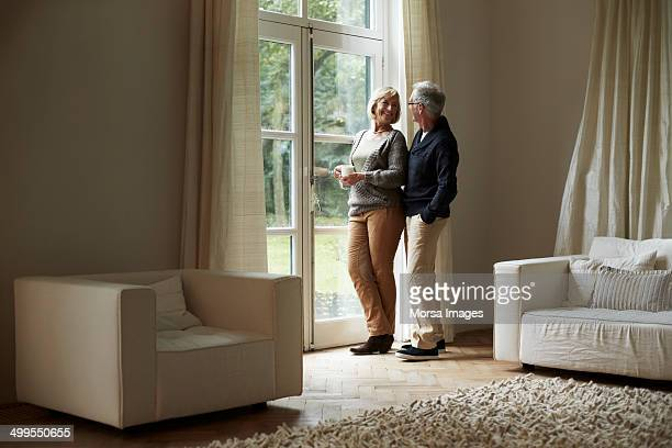 Happy senior couple standing by house door