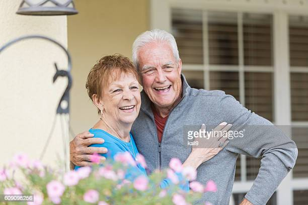 Happy senior couple standing on porch of home