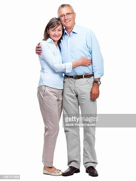 Happy senior couple standing together against white background
