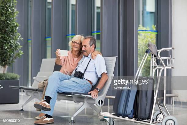 Happy senior couple taking selfie in airport