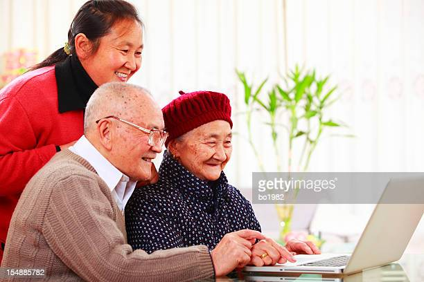happy senior couple use laptop