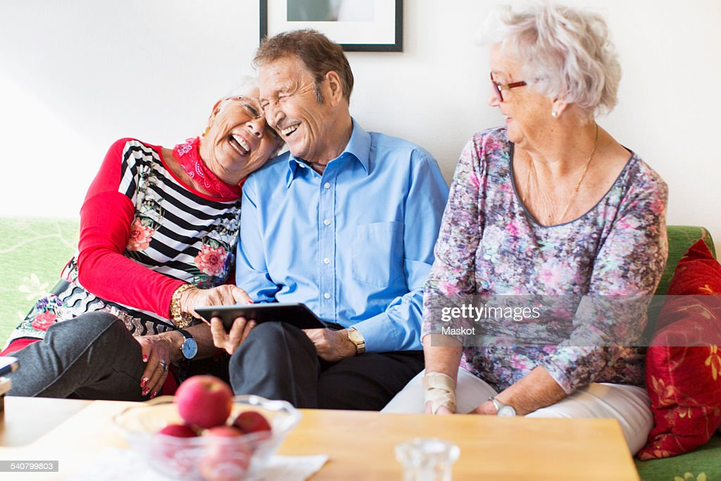 Happy senior couple using digital tablet by female friend in nursing home