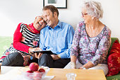 Happy senior couple using digital tablet by female friend in nursing home