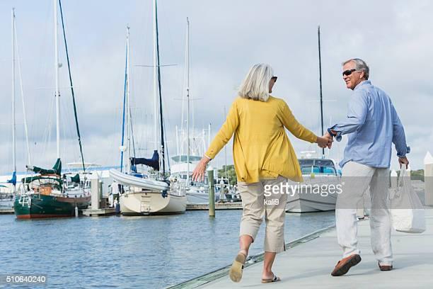 Happy senior couple walking along harbor holding hands