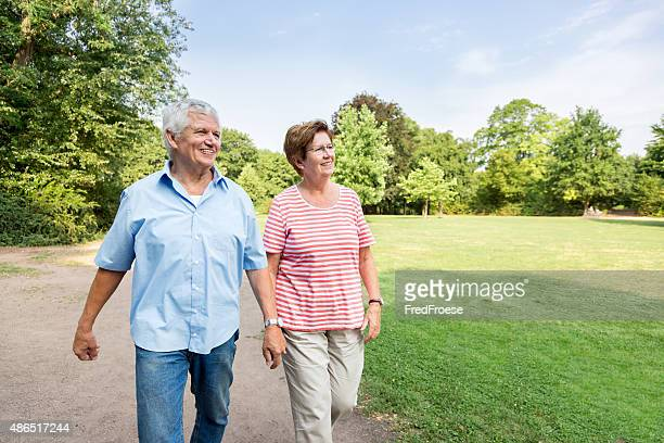 Happy senior couple walking outdoors in the park