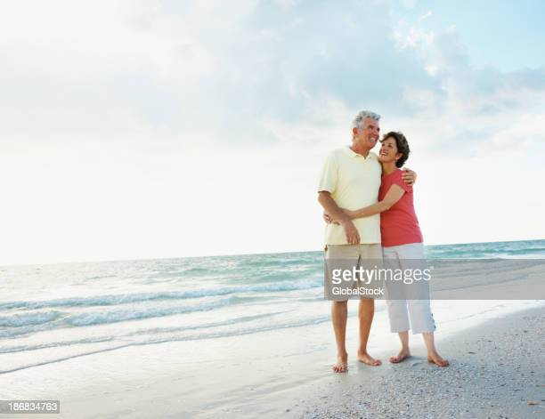 Happy senior couple with arms around at a beach