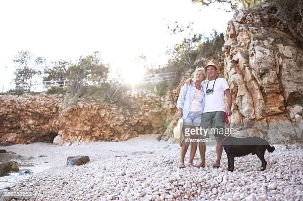 Happy senior couple with dog on the beach