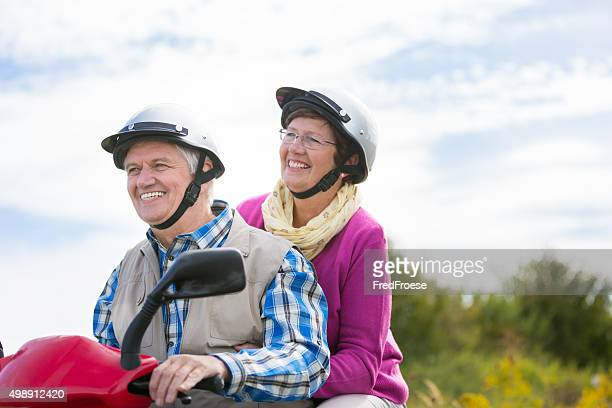 Happy senior couple with motor scooter on a sunny day