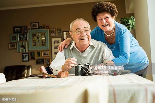 Happy senior couple with old camera at home