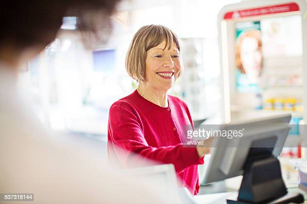 Happy senior customer at pharmacy checkout counter