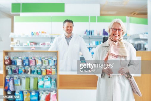 Happy senior customer in a pharmacy : Stock Photo